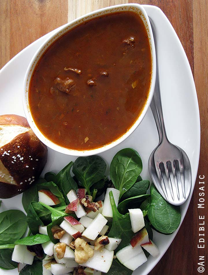 Gulaschsuppe (German Goulash Soup) in White Bowl with Side Salad