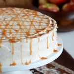 Caramel Apple Cake on White Cake Stand with Apples in Background