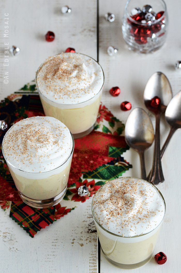 Eggnog Pudding on White Wooden Table with Festive Christmas Fabrics and Small Jingle Bells