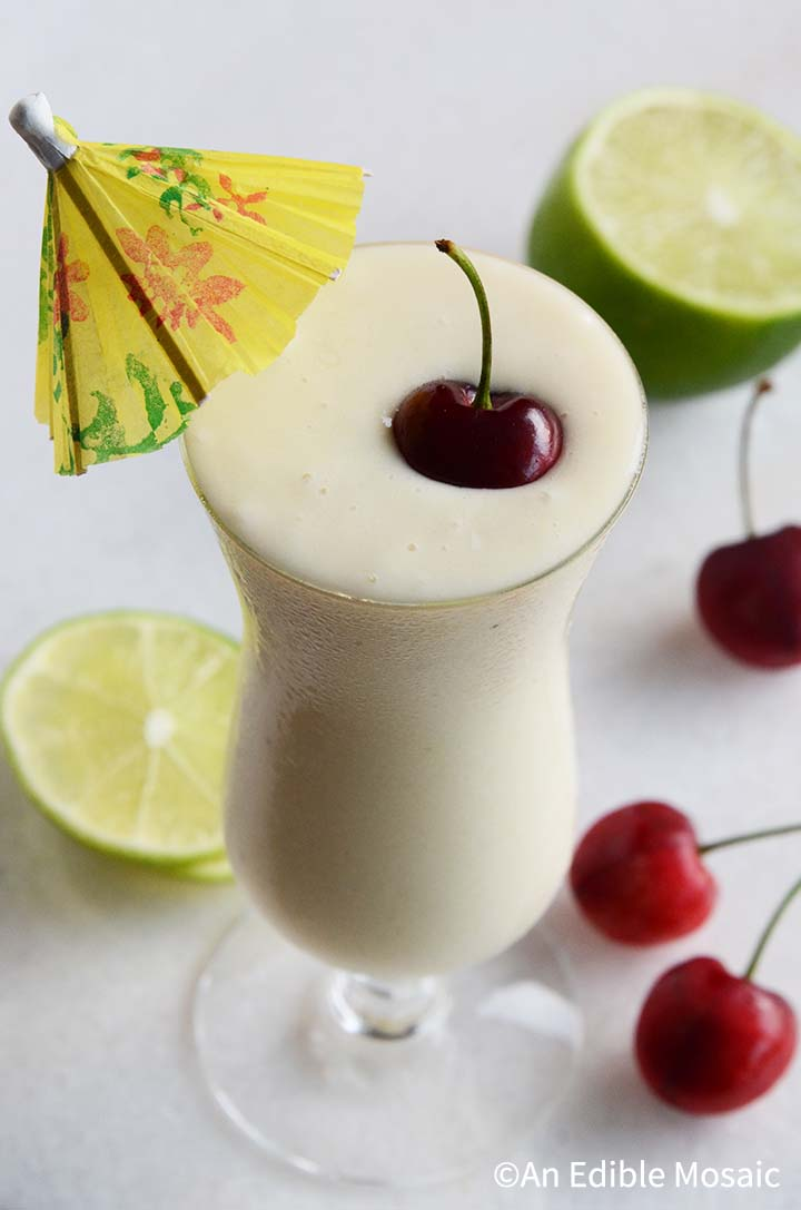 Healthy Pina Colada Smoothie with Fresh Cherry and Yellow Umbrella Garnish