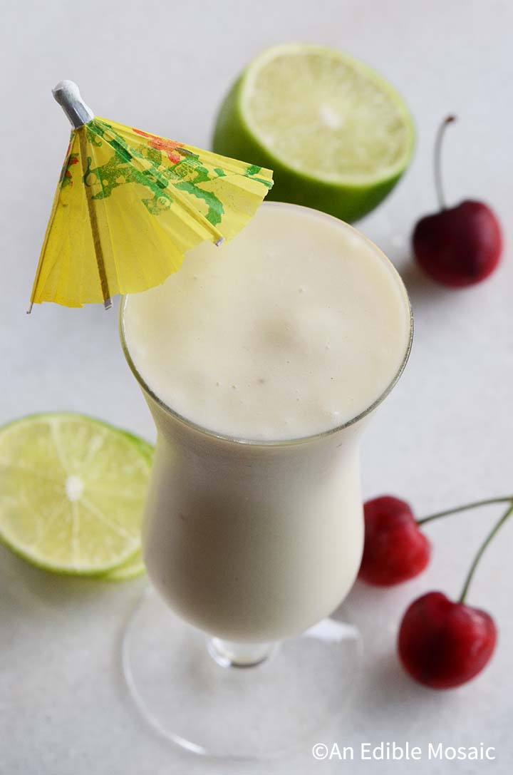 Pina Colada Drink on White Marble Countertop with Lime and Fresh Cherries