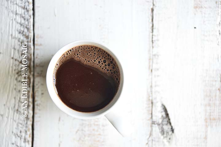 Close Up Overhead View of Mug of Drinking Chocolate on White Wooden Farmhouse Table