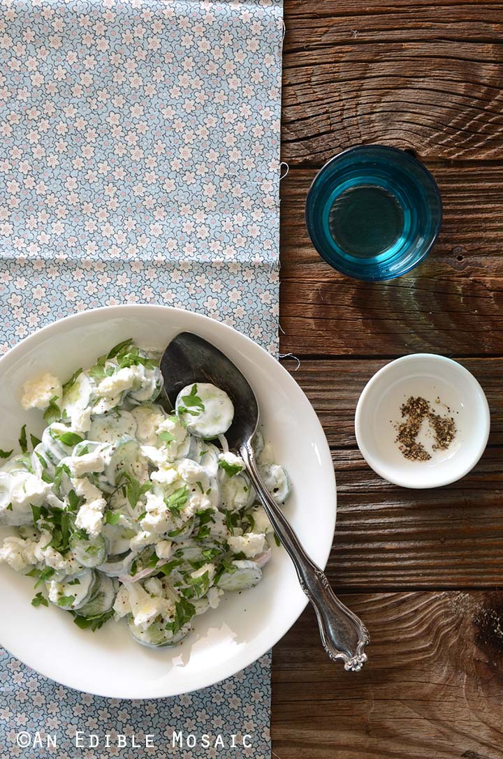 Creamy Cucumber Salad Recipe in Bowl on Flowered Fabric on Wooden Table