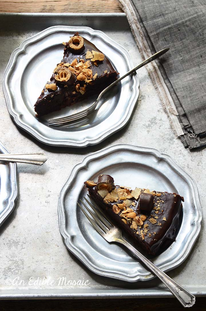 Two Slices of Chocolate Hazelnut Cake on Metal Plates with Vintage Forks
