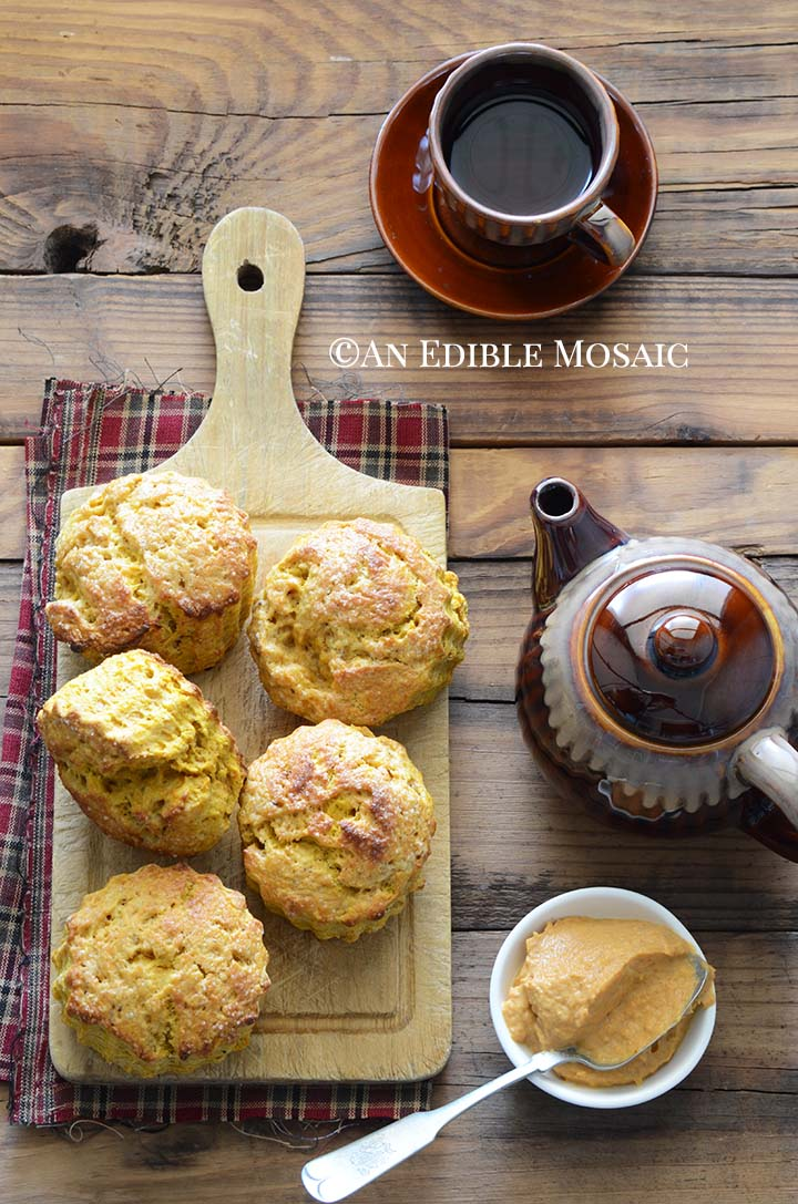 Overhead View of Pumpkin Scones on Bread Board on Wooden Table with Teapot