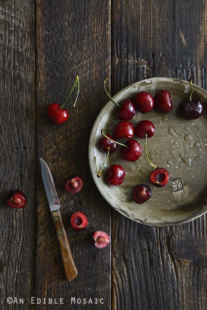 Cherries on Stoneware Plate on Dark Wood Table