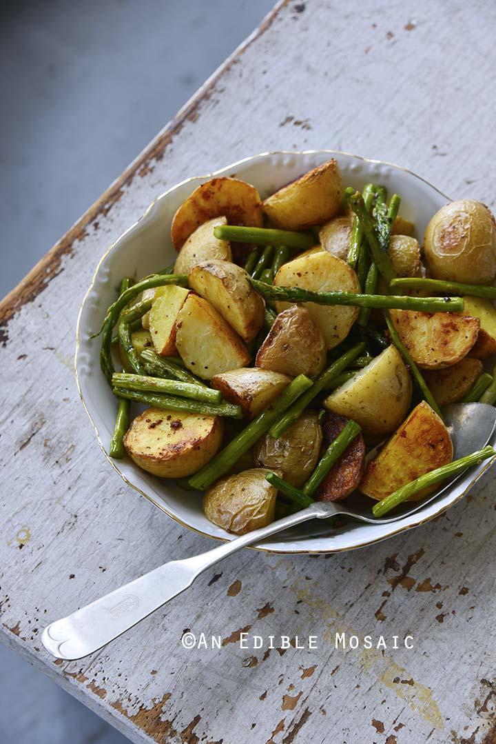 Garlic-Roasted New Potato and Asparagus Salad in a Bowl on a Rustic White Background