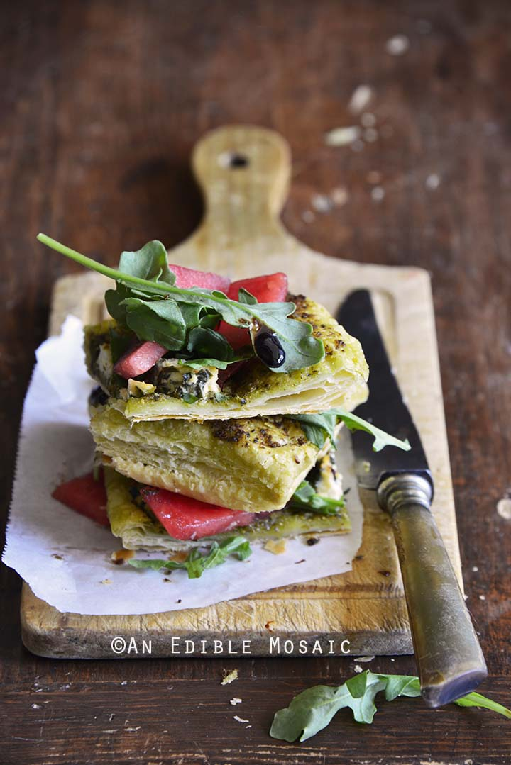 Garlic and Chive Goat Cheese and Pesto Puff Pastry Tart with Arugula, Watermelon, and Strawberry-Balsamic Drizzle on a Wooden Board