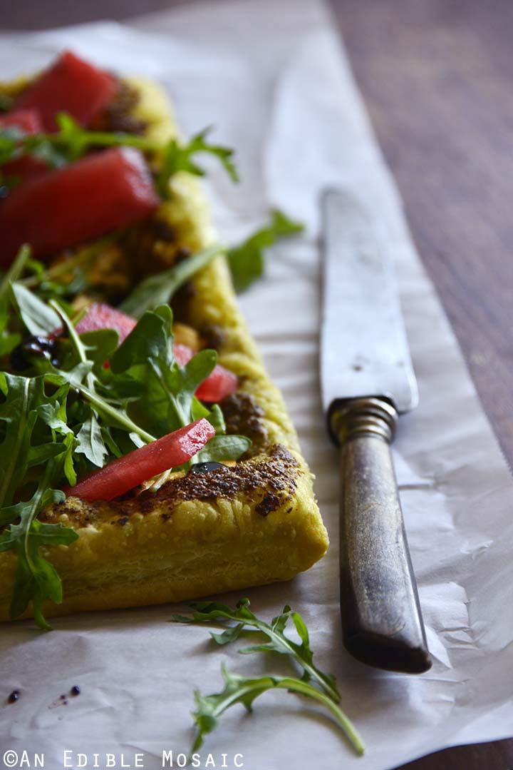 Garlic and Chive Goat Cheese and Pesto Puff Pastry Tart with Arugula, Watermelon, and Strawberry-Balsamic Drizzle on Parchment Paper