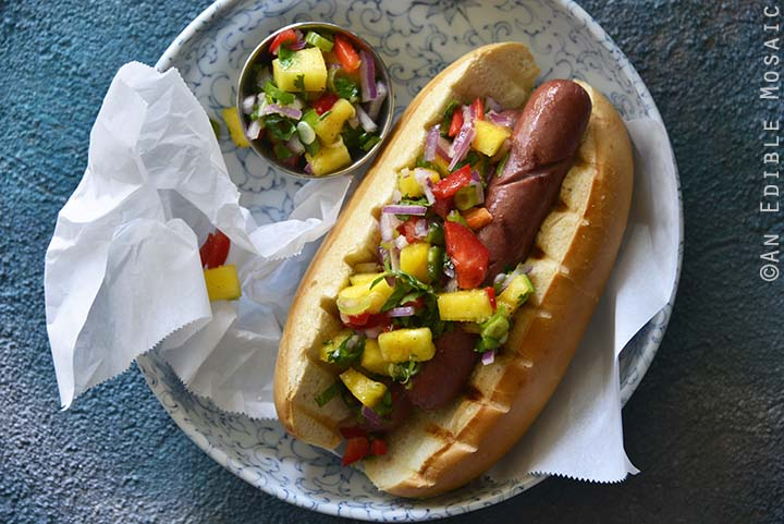 Hot Dogs with Hawaiian-Inspired Pineapple Jalapeno Teriyaki Relish on Blue Background Top View Horizontal