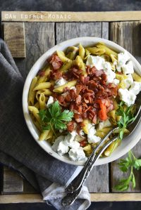 Warm Caramelized Leek Pasta Salad with Bacon and Goat Cheese on Wooden Background Top View