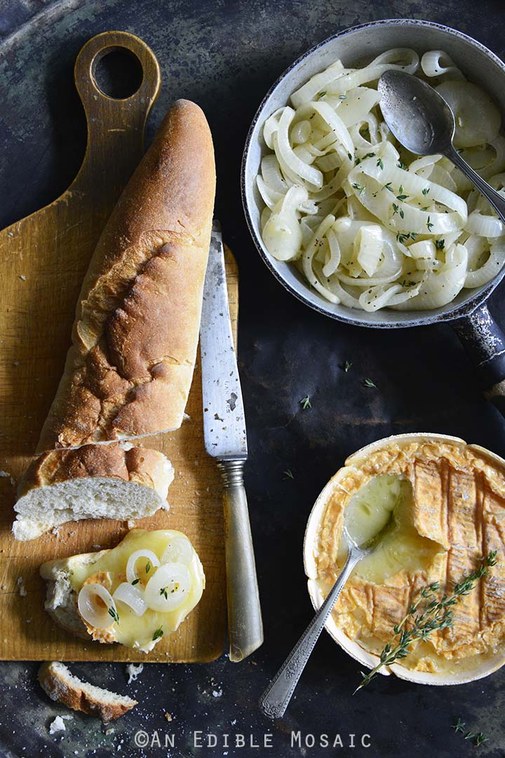 Spread of Baked Schloss Cheese with Melted White Wine Onions with Baguette