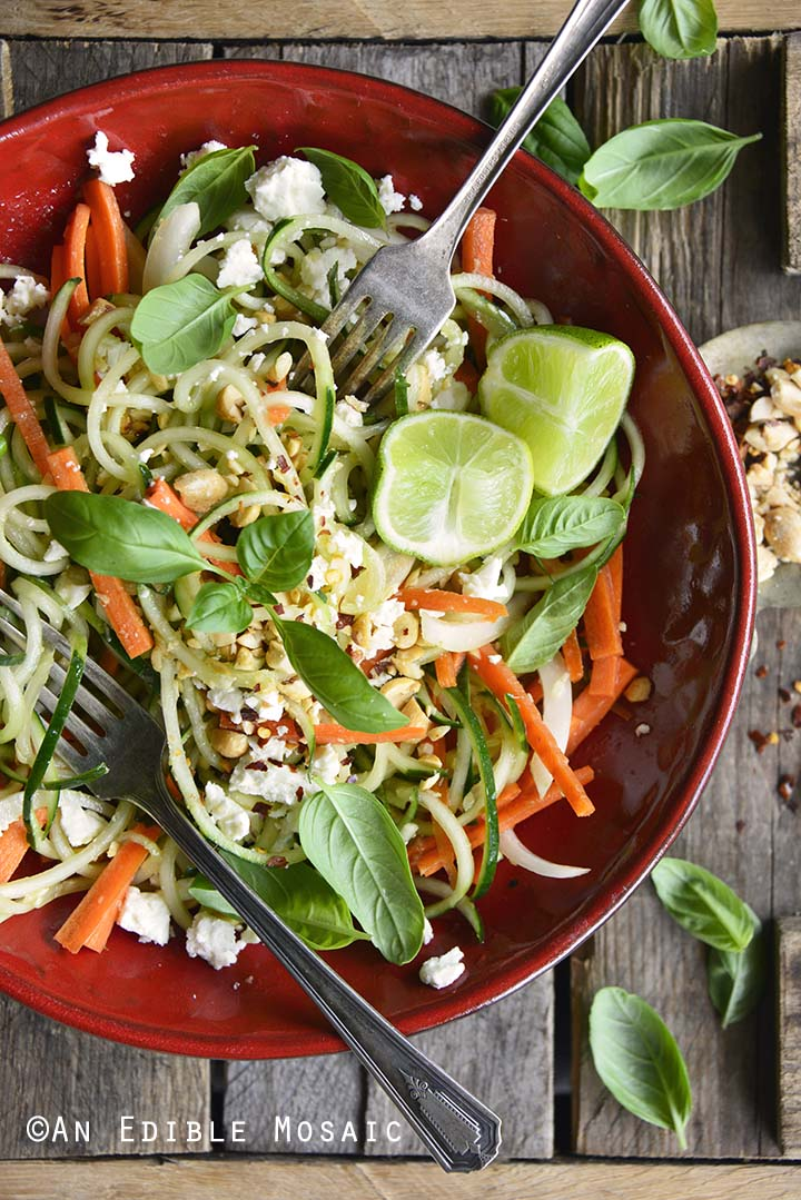 Low Carb Spiralized Cucumber Salad with Peanuts, Basil, and Ginger Miso Dressing on Wooden Table