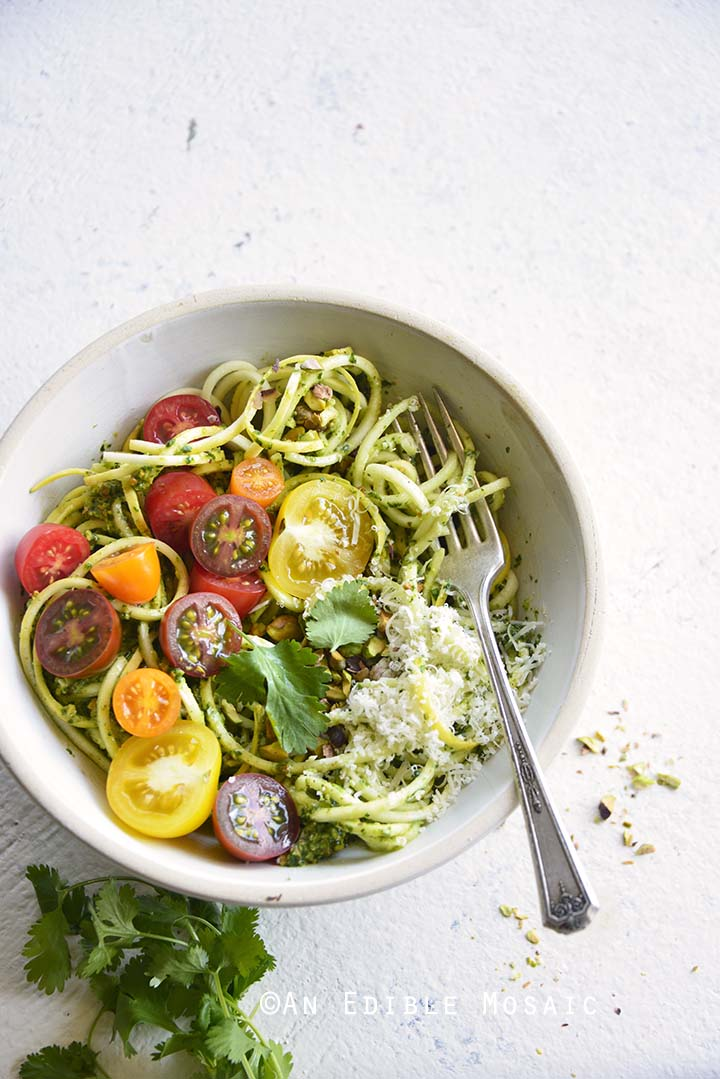 Low Carb Spiralized Yellow Squash Noodles with Tomatoes, Pesto, and Parmesan on White Table