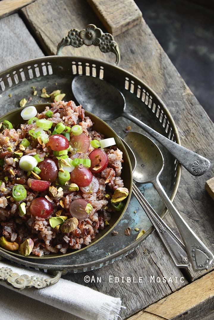 Red Rice Recipe with Grapes and Pistachios on Wooden Crate