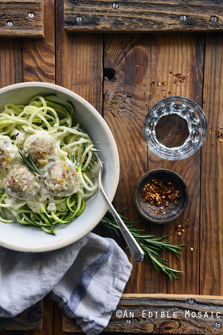 Bowl of Low Carb Cheesy Turkey Meatballs with Rosemary Cream Sauce on Wooden Background