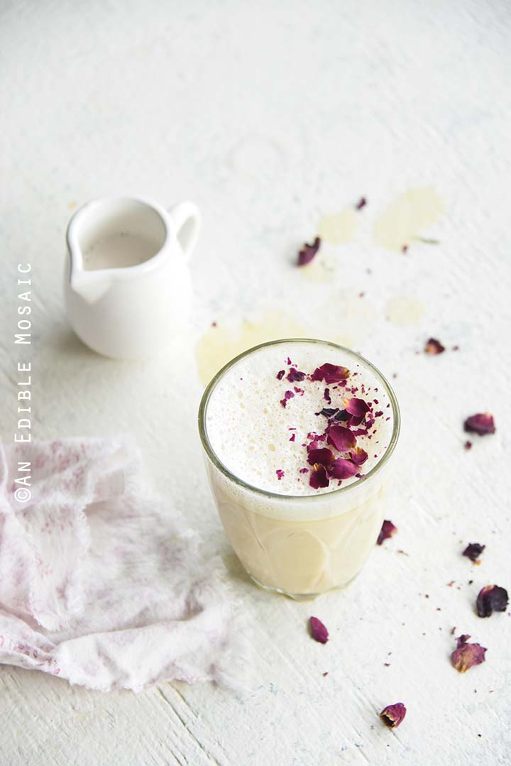 Rose Tea Latte with Vanilla Rooibos on White Table with Scattered Rose Petals