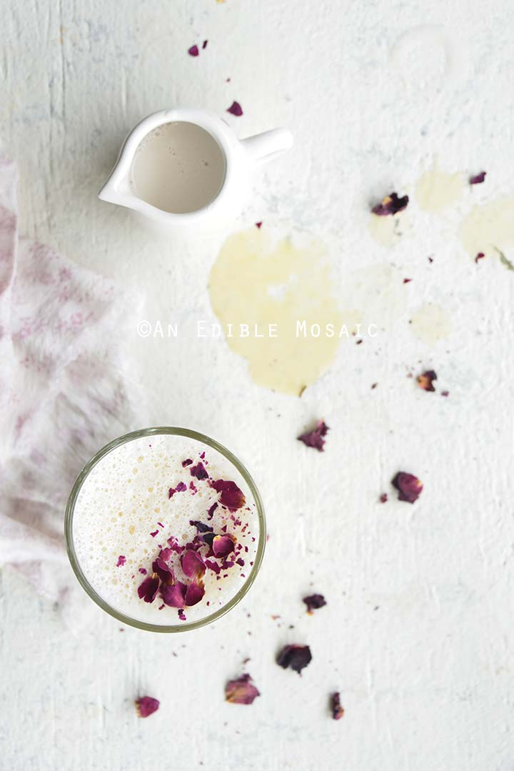 Overhead View of Rose Tea Latte with Vanilla Rooibos on White Table with Spilled Tea