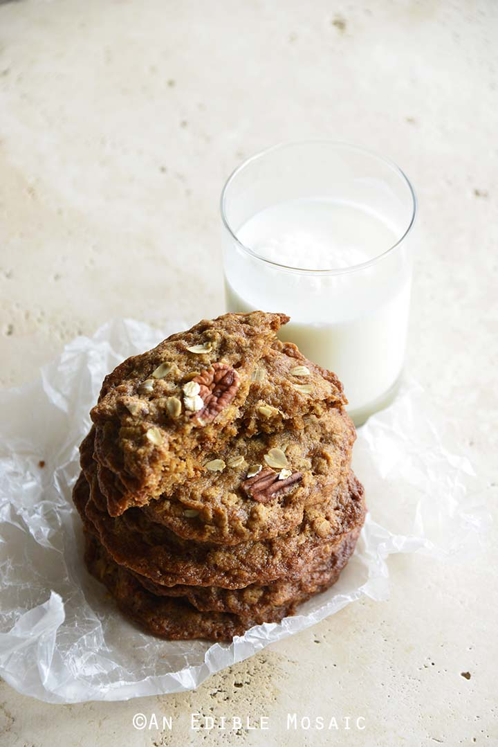 Chewy Cinnamon Pecan Brown Butter Oatmeal Cookies and Milk Glass on Creamy White Marble Countertop