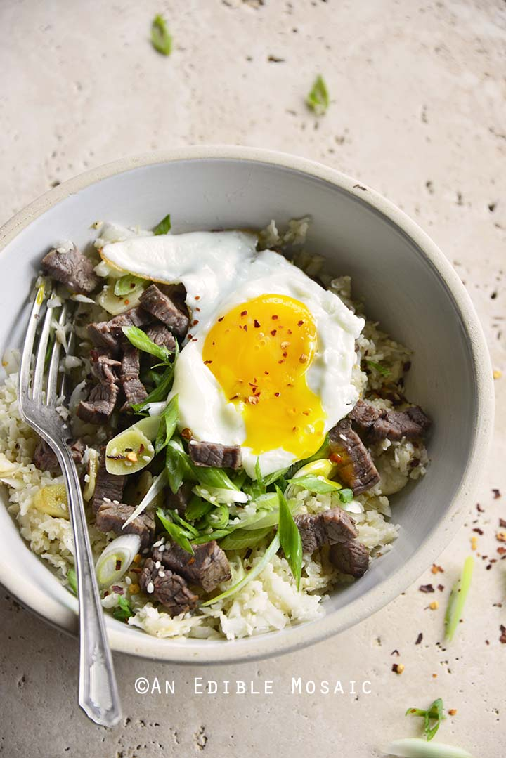 Overhead View of Low Carb Chili Garlic Steak Rice Bowl with Fried Egg and Runny Yolk