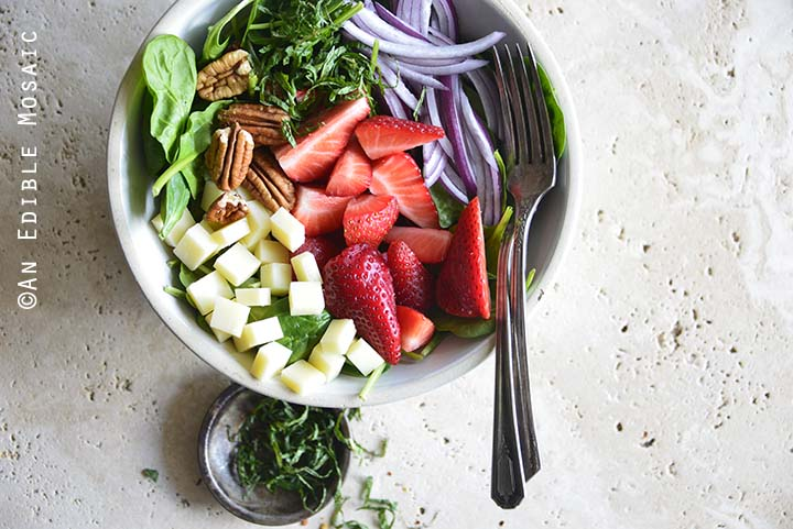 Close Up of Spinach Strawberry Salad with Small Dish of Mint
