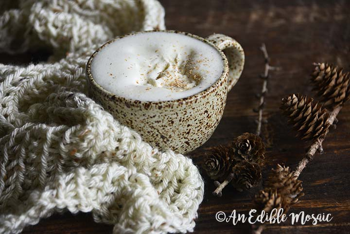 Keto Eggnog Latte Next to Creamy Cozy Scarf with Pinecones on Wooden Table