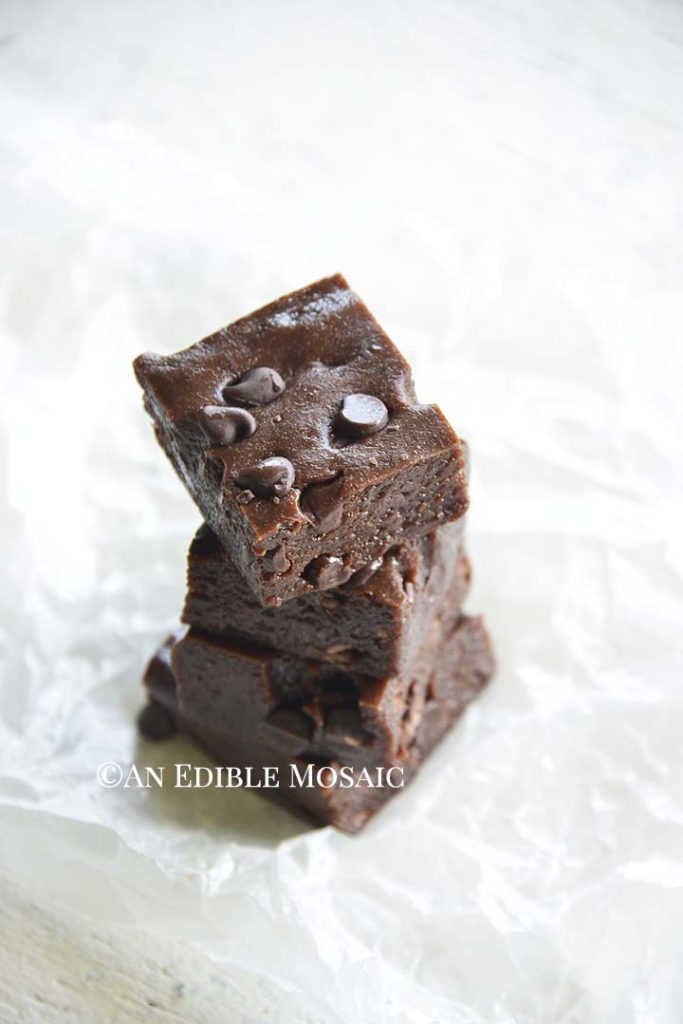 Front View of Several Fudgy Double Chocolate Protein Bars Stacked on Wax Paper