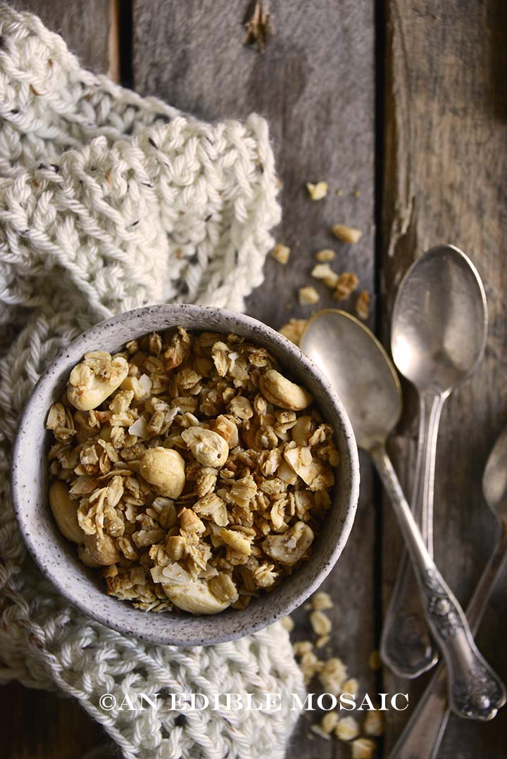 Top View of Healthy Granola Recipe with Cashews and Coconut in White Bowl with Scarf and Vintage Spoons on Wooden Table