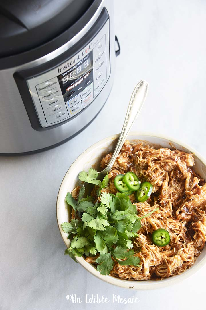 Instant Pot Pulled BBQ Chicken in White Bowl with Instant Pot in Background