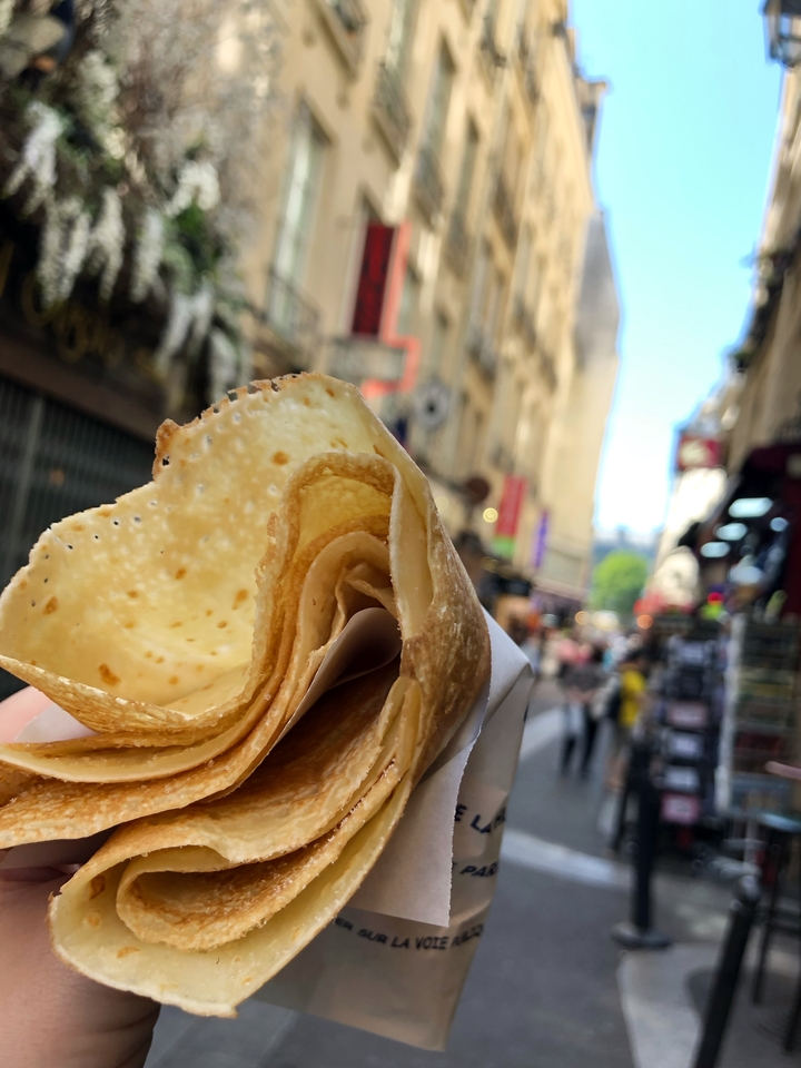 Hand Holding Crepe with Paris Street in Background