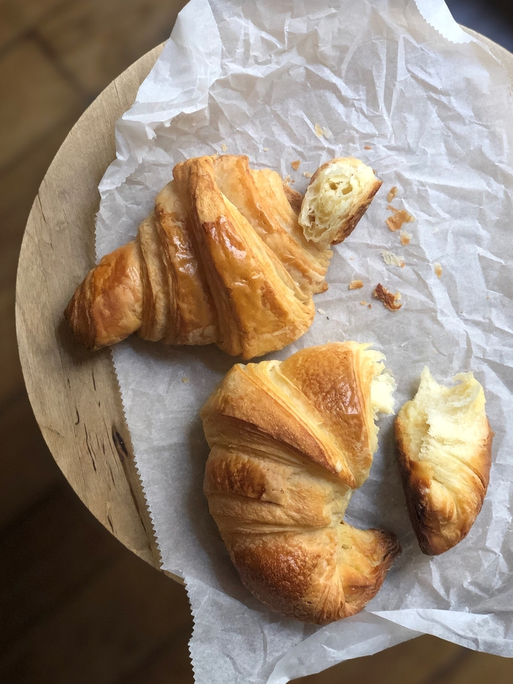 Croissant Beurre and Croissant Naturel on Parchment Paper on Wooden Table