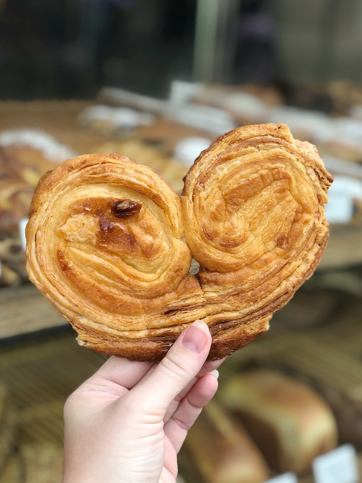 Hand Holding Palmier in Front of Bakery Window