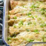 Creamy Chicken and Kale Enchiladas with Salsa Verde in White Casserole Dish