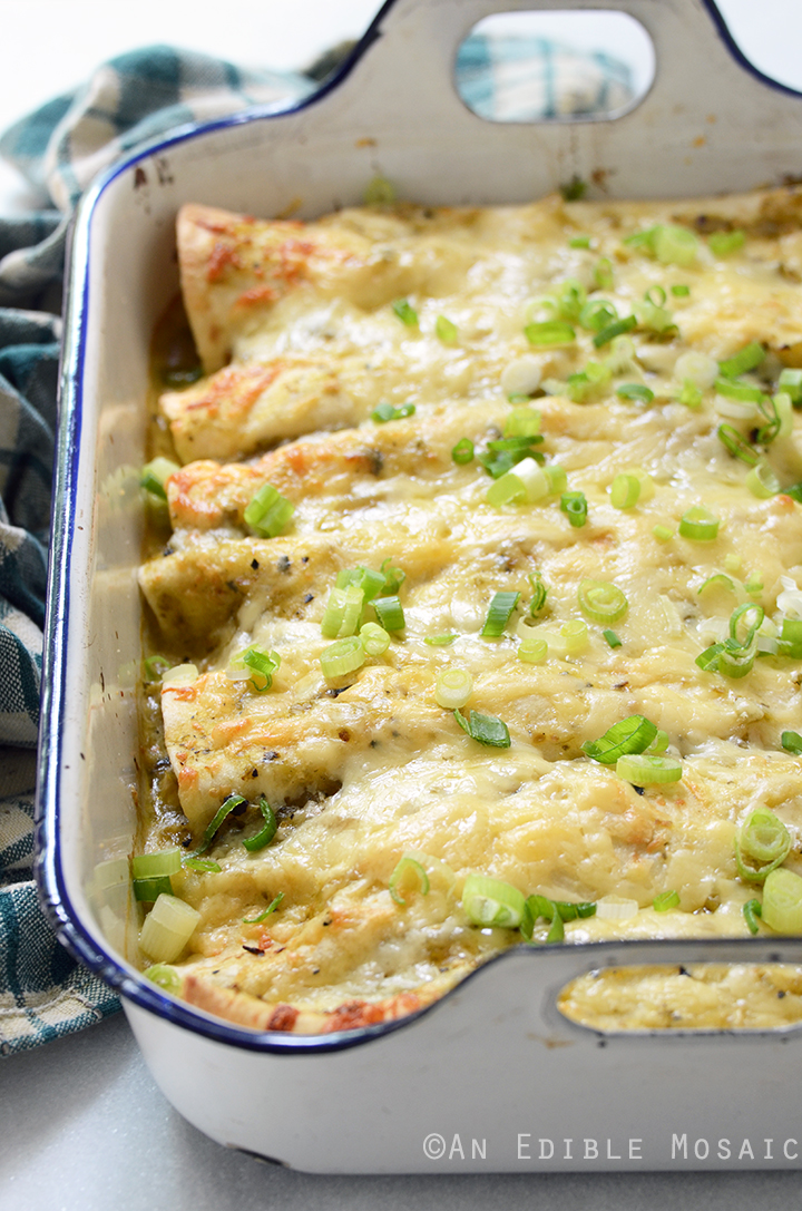 Creamy Chicken and Kale Enchiladas with Salsa Verde in White Casserole Dish