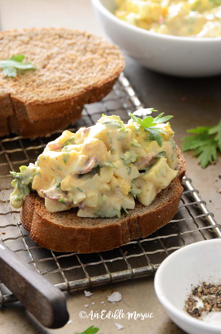 Assembling Egg Salad with Bacon and Creamy Honey Mustard Dressing Into a Sandwich