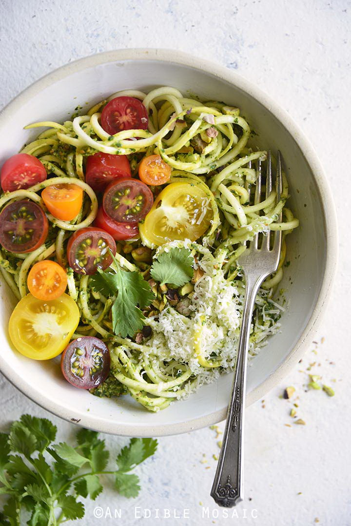 Low Carb Spiralized Yellow Squash Noodles with Tomatoes, Pesto, and Parmesan in White Bowl on White Table