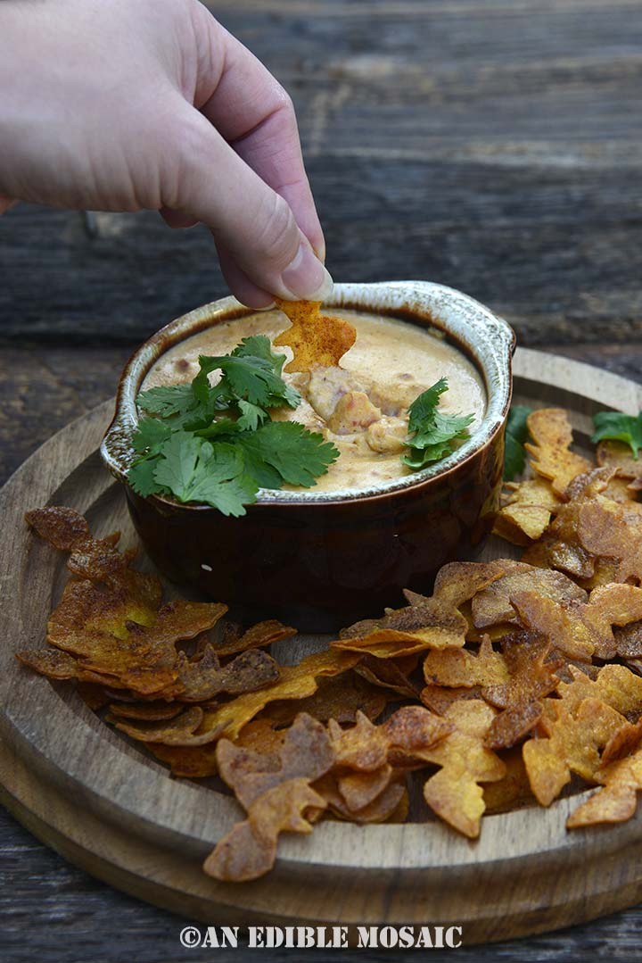 Hand Dipping Into Pumpkin Queso Dip with Spooky Dipper