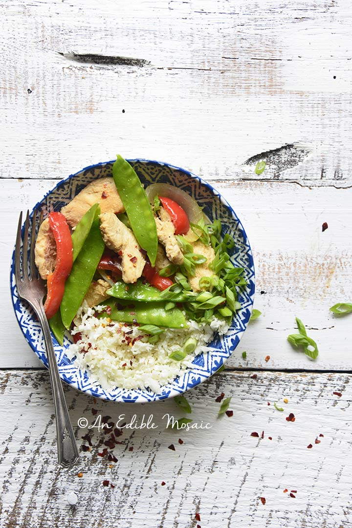 Overhead View of Healthy Sweet and Sour Chicken Stir Fry Recipe in Blue and White Bowl on White Table