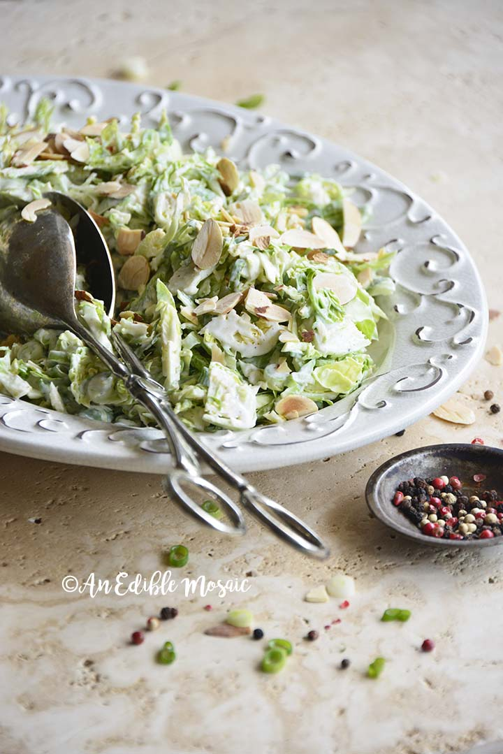 Front View of Brussels Sprout Salad on White Vintage Platter with Peppercorns in Foreground
