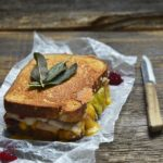 Grilled Cheese Thanksgiving Leftovers Sandwich on White Parchment Paper with Paring Knife