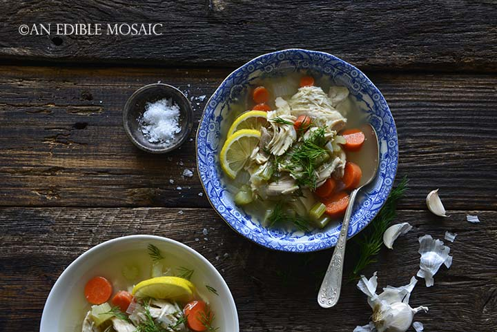Homemade Chicken Soup Recipe in Blue and White Bowl with Vintage Spoon and Garlic Peels on Wood Table