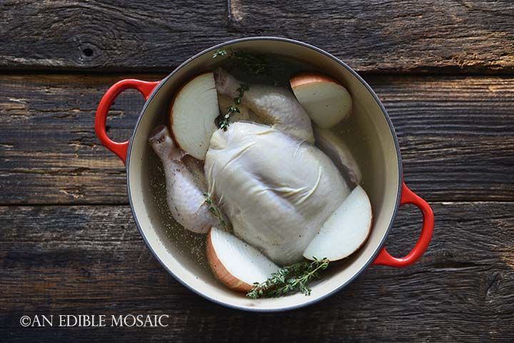 Making Chicken Stock with Chicken and Vegetables in Red Dutch Oven Pot on Wooden Table