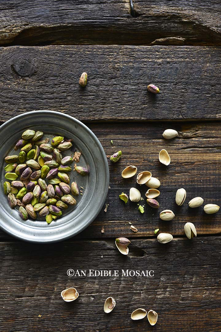 Pistachios in Small Metal Bowl on Wooden Table