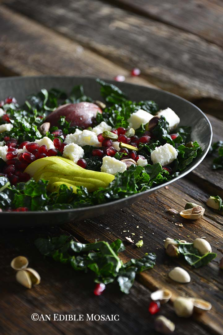 Front View of Winter Kale Salad with Pomegranate in Metal Bowl on Rustic Wood Table