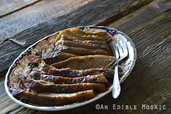 Braised Beef Brisket on Serving Platter on Dark Wooden Table