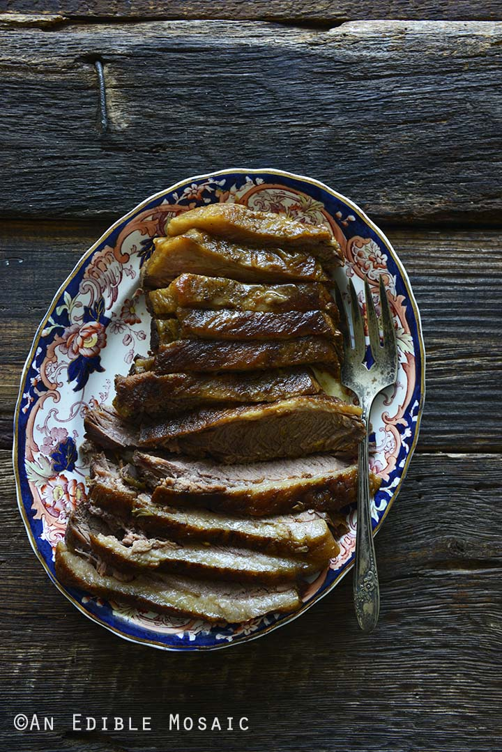 Top View of Beef Brisket on Platter with Vintage Fork on Dark Rustic Wooden Table