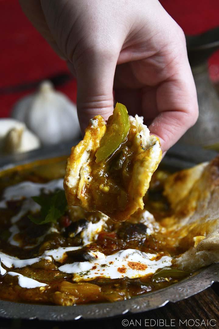 dipping flatbread into borani banjan