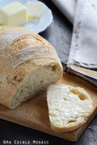 No Knead Bread Loaf on Cutting Board with a Buttered Slice of Bread