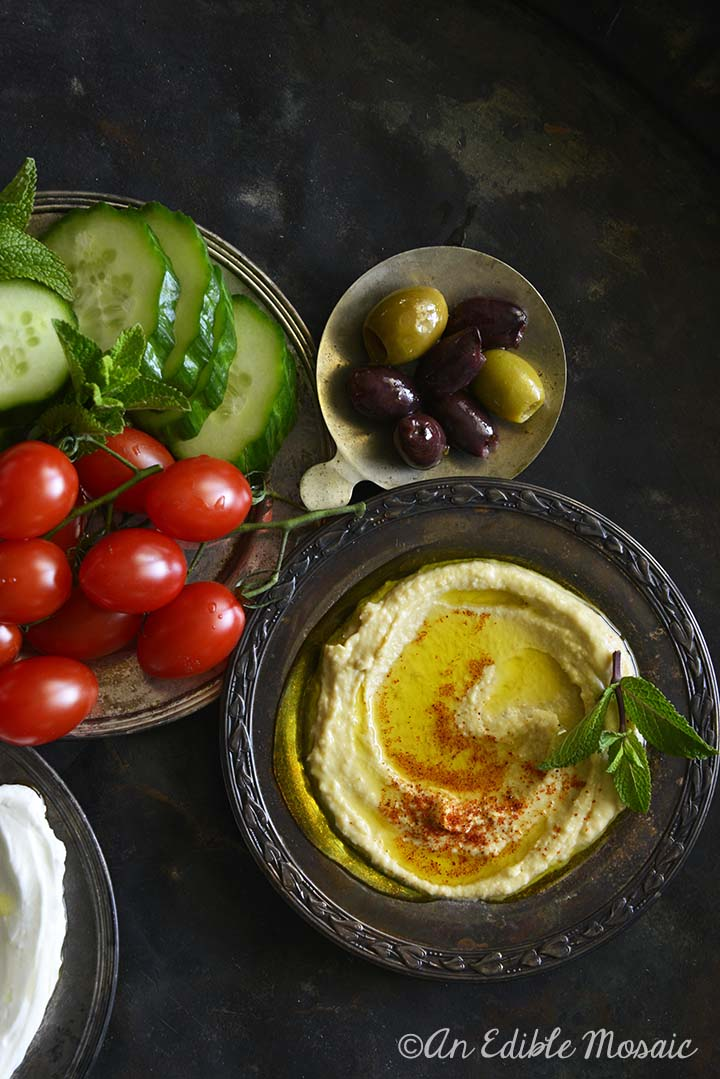 Hummus on Dark Tray with Olives and Cherry Tomatoes
