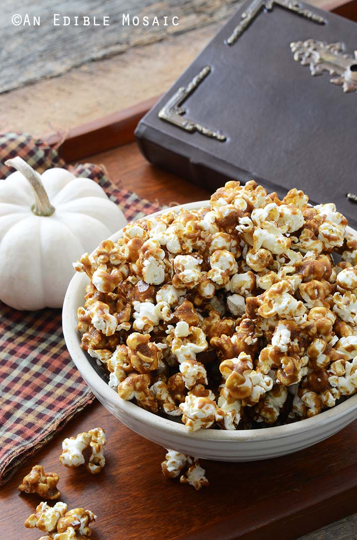 Butterbeer Popcorn in White Ceramic Bowl with Small White Pumpkin and Old Book on Wooden Tray